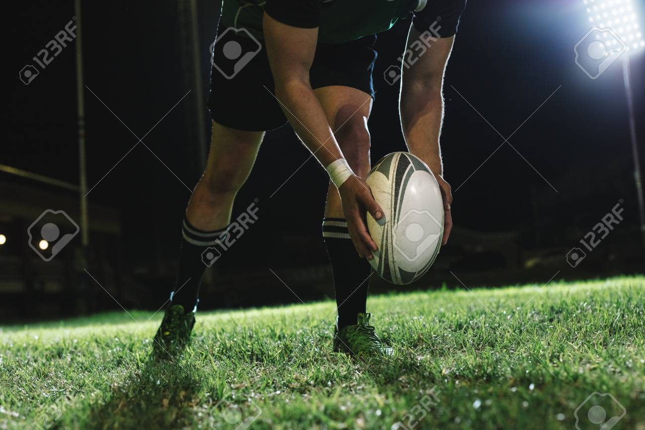 Rugby player dropping the ball to the ground for kicking as it touches the ground. - 116932442