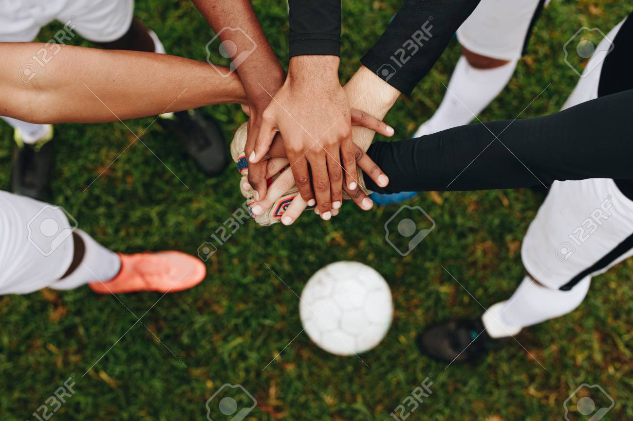 Top view of hands of players placed one over the other standing in a huddle. Players standing in a huddle joining their hands together in the centre with a soccer ball on the ground. - 115978428