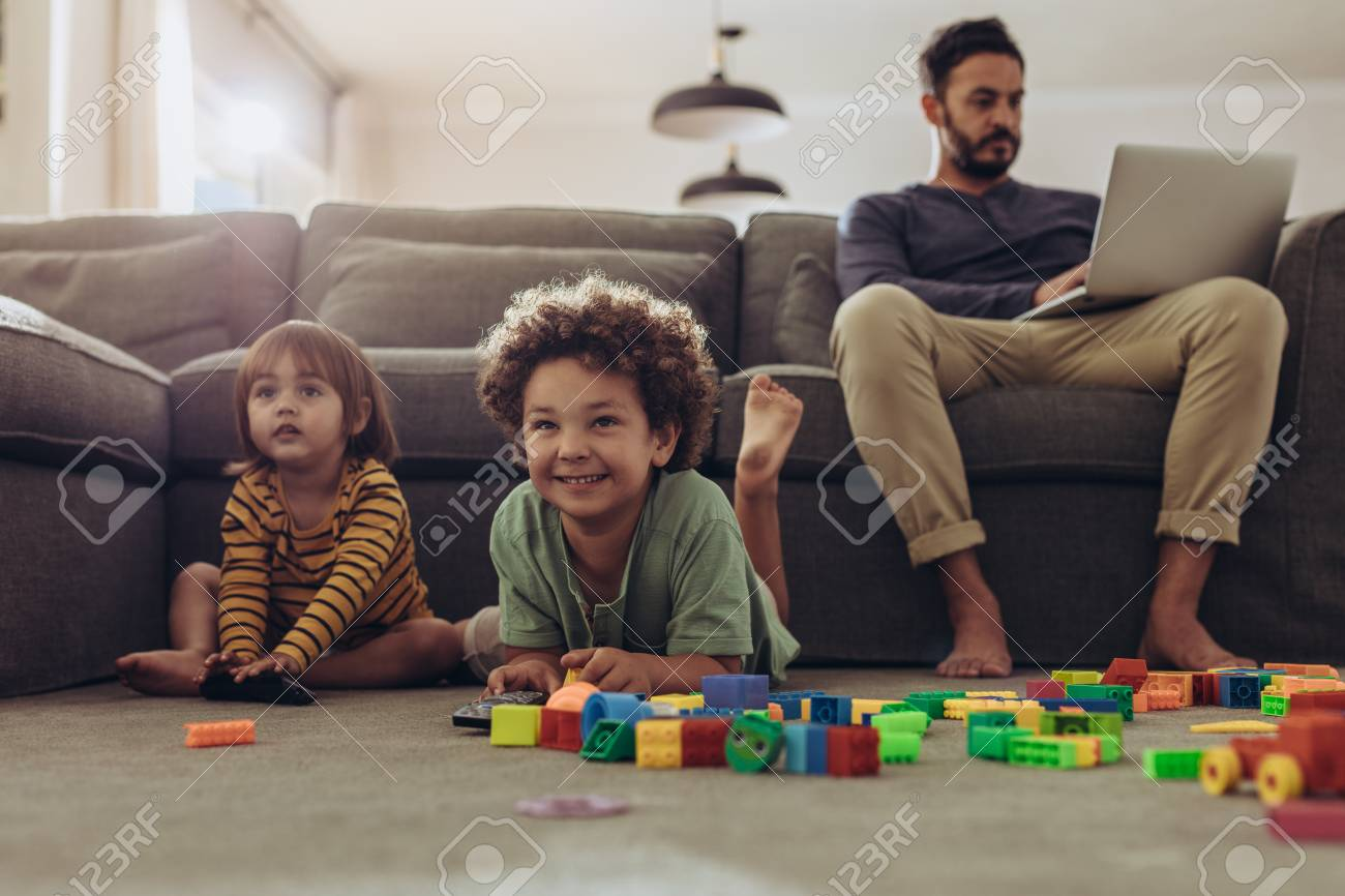 Smiling kids playing with building blocks and watching television at home. - 116176059