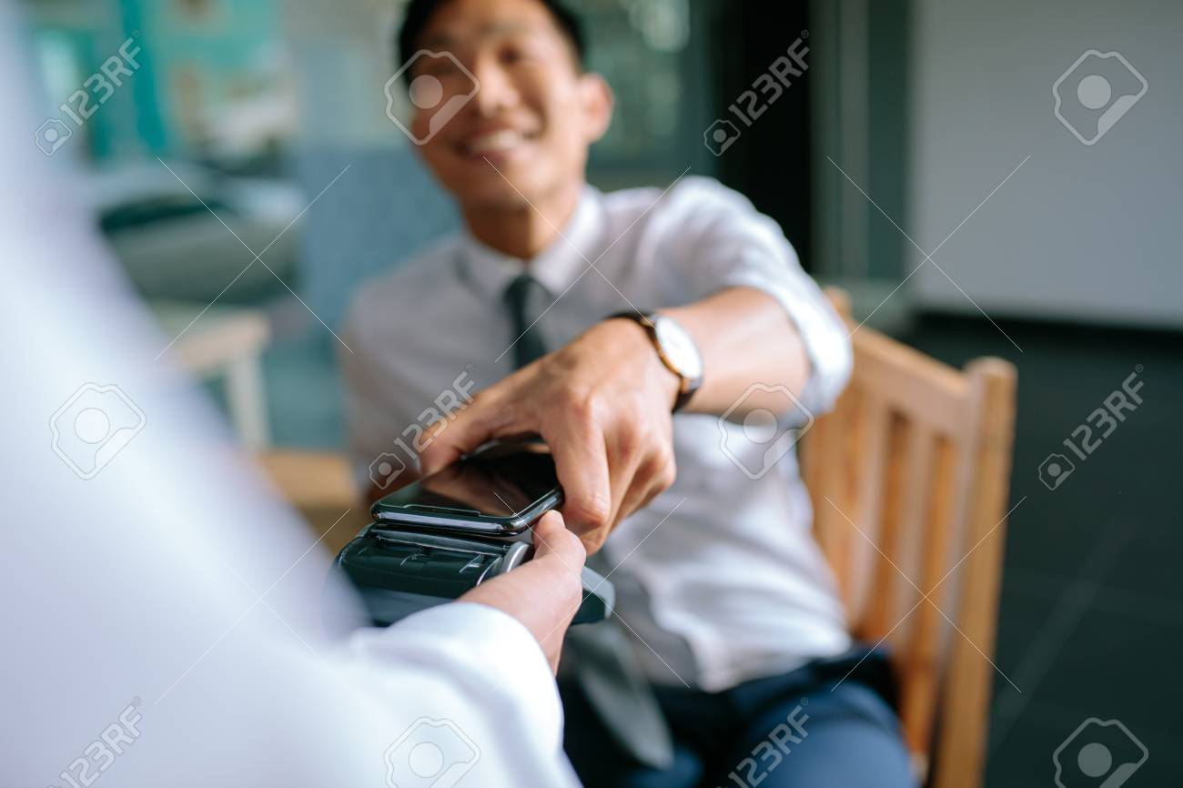 Businessman paying bill through smartphone using NFC technology in restaurant. Closeup of male hand holding his mobile phone over a card reader machine for doing the payment. - 116932199