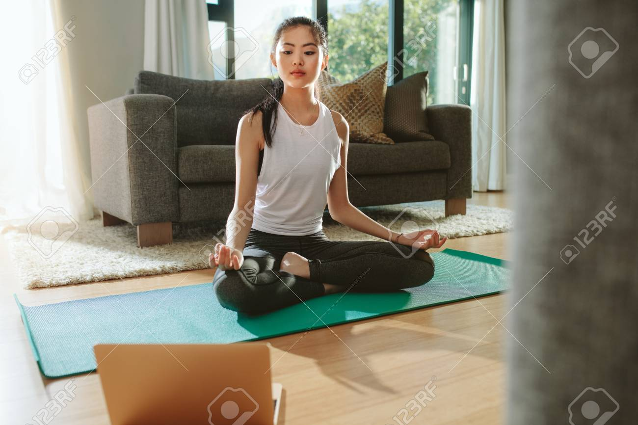 Fit woman doing yoga exercise while watching tutorial on laptop at home. Attractive chinese woman exercising on a mat and watching instructional videos on laptop. - 118799630
