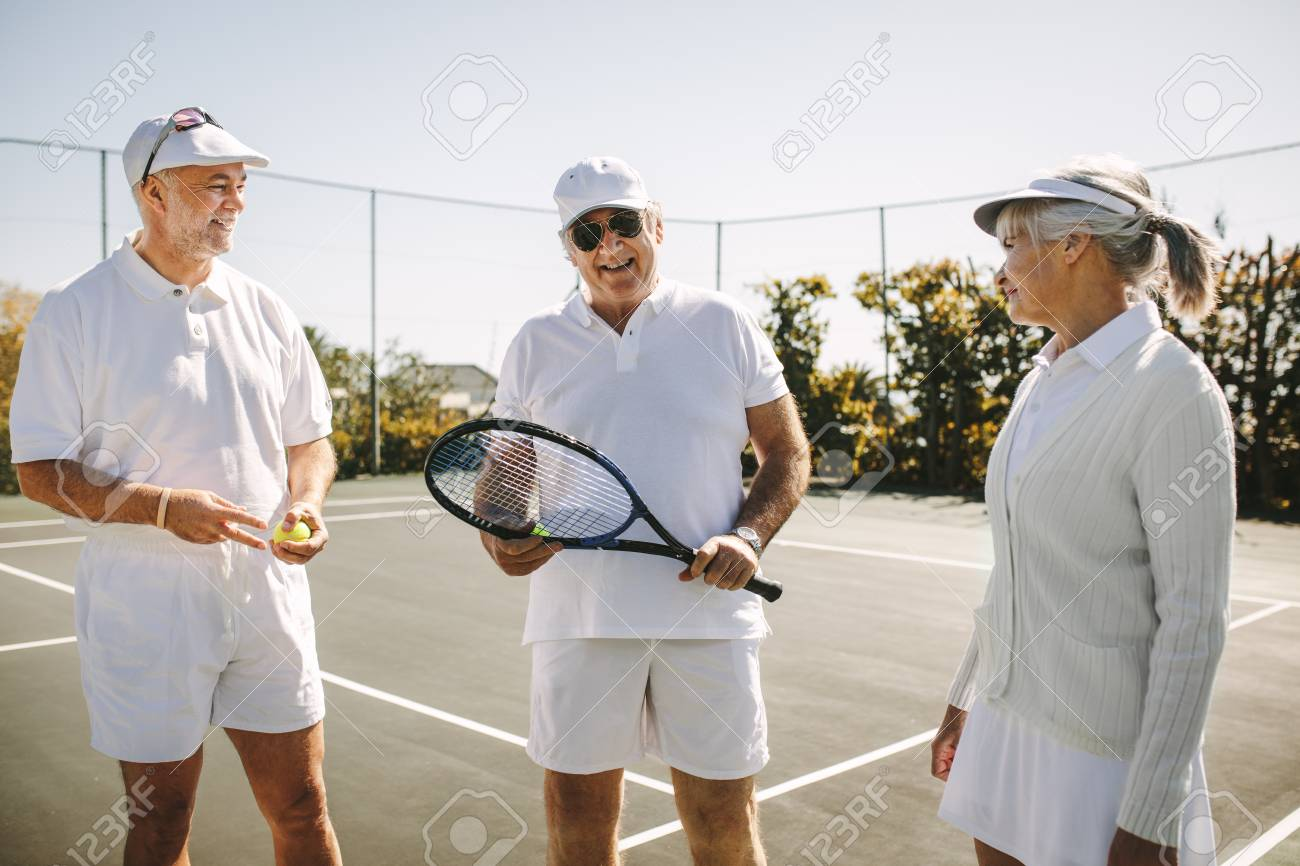 Cheerful Men In Tennis Wear Talking To A Senior Woman Standing Stock Photo Picture And Royalty Free Image Image 118799646