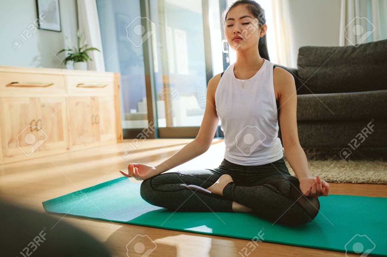 Fit young female meditating in lotus pose at home. Beautiful woman doing yoga exercise indoors. - 118800838