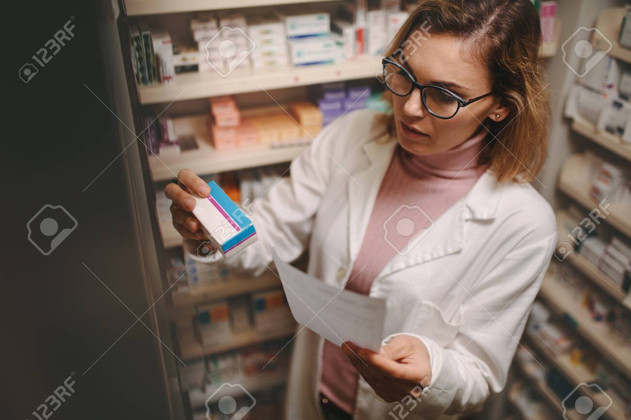 Chemist with a prescription searching right medicine on shelves in pharmacy. Female pharmacist holding prescription checking medicine in pharmacy. - 119566447