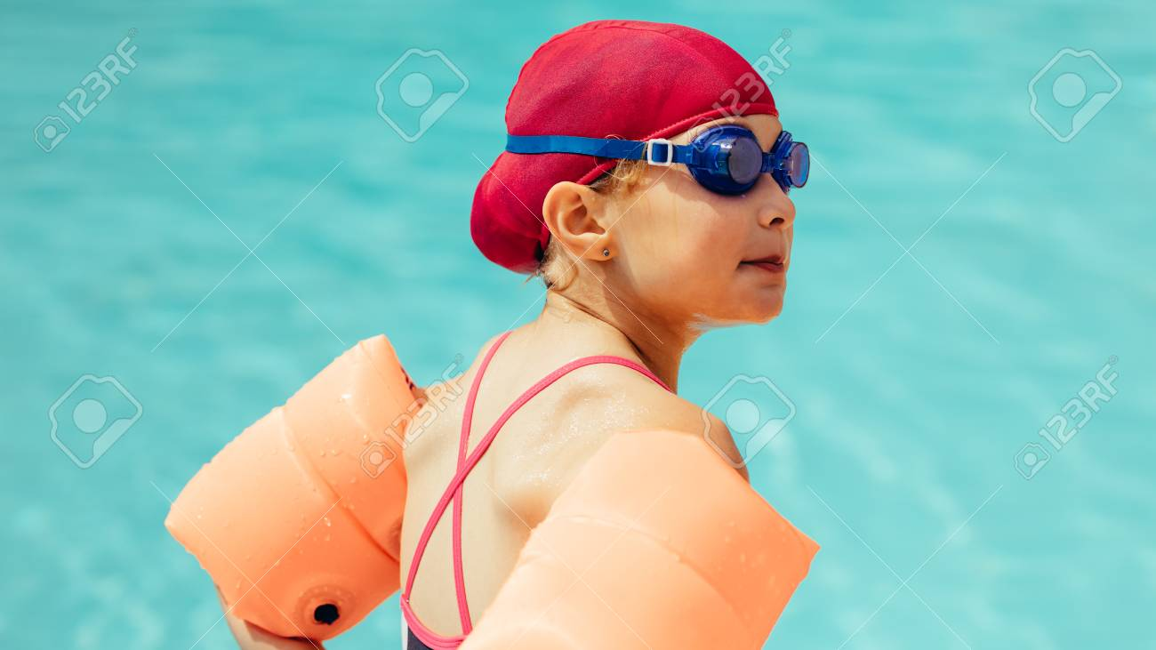 Rear view of a girl in swimming gear standing by swimming pool...