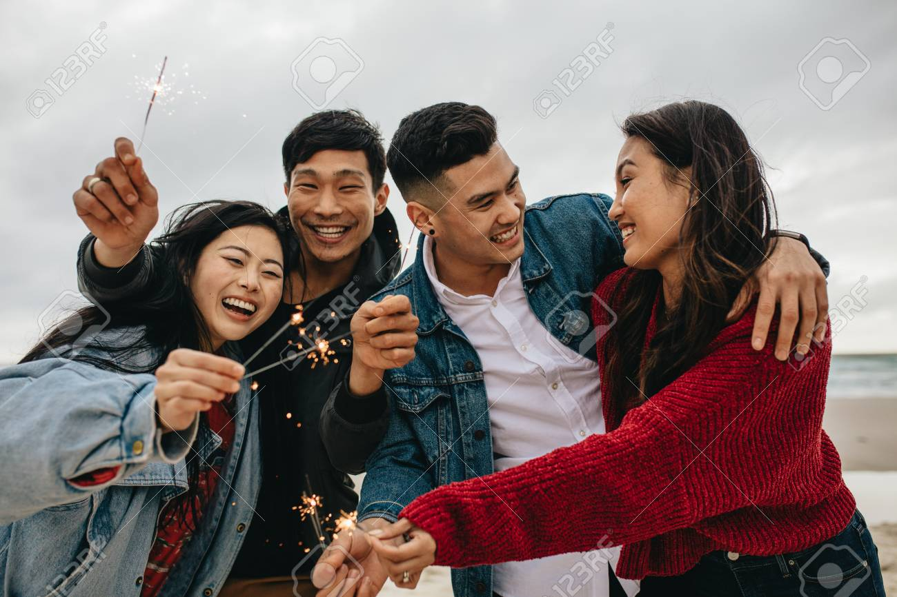 Diverse group of young people celebrating new year's day at the beach. Young asian people having fun with sparklers outdoors at the sea shore. - 119566777