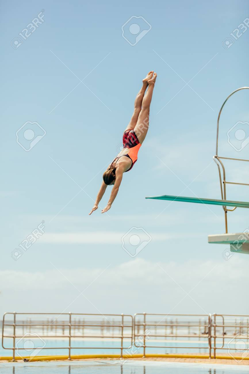 Woman diving into the pool from spring board. Female diver diving upside down into the swimming pool. - 120521058