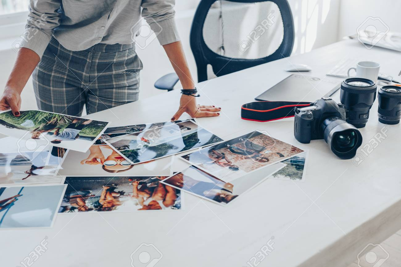 Woman standing at her desk and choosing the best images from photoshoot. Female photographer looking at the photo prints on table. - 120521227