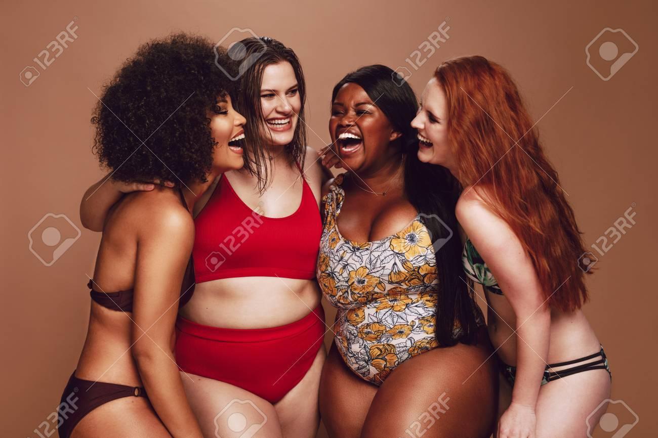 Multi-ethnic women in swimwear having fun together in studio. - 120521467