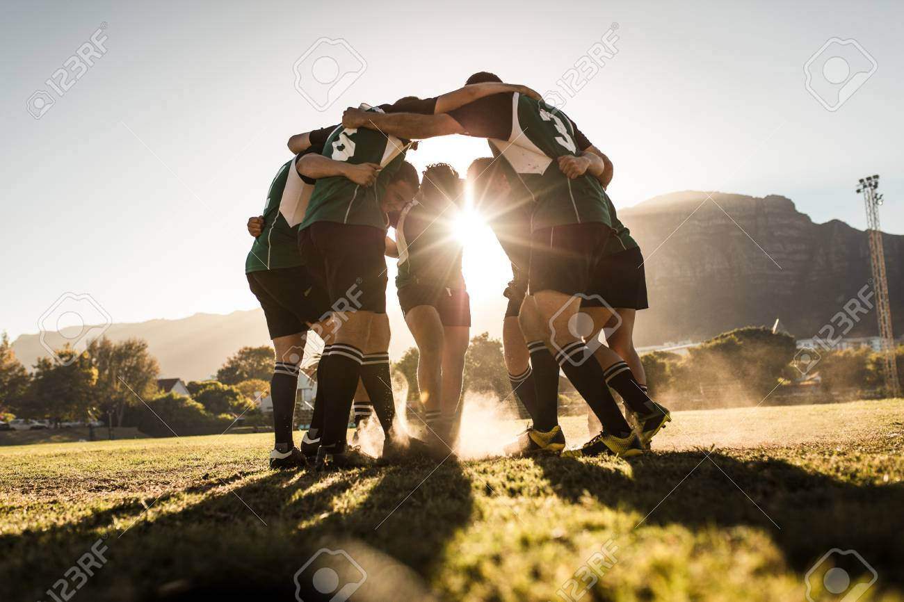Rugby team standing in a huddle and rubbing their feet on ground. Rugby team celebrating victory. - 120521746