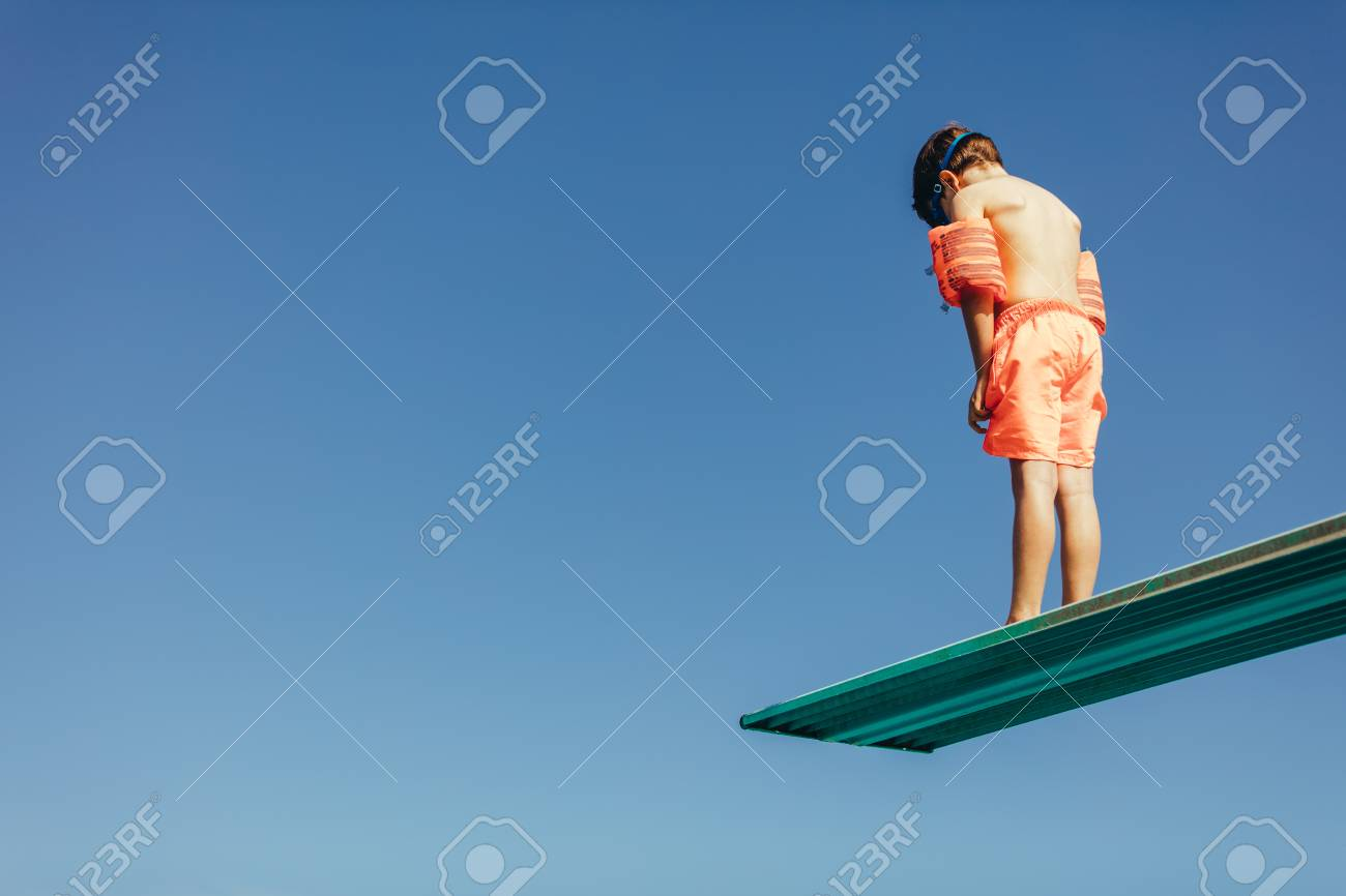Low angle shot of boy with sleeves floats on diving board preparing for dive in the pool. Boy standing on diving spring board against sky. - 120574384