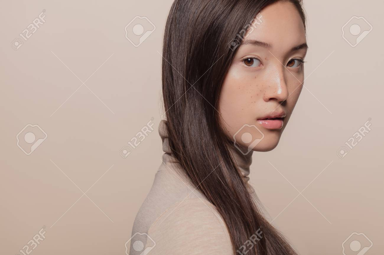 Portrait of woman with straight brown hair. Asian woman with a long hair looking at camera. - 122865699