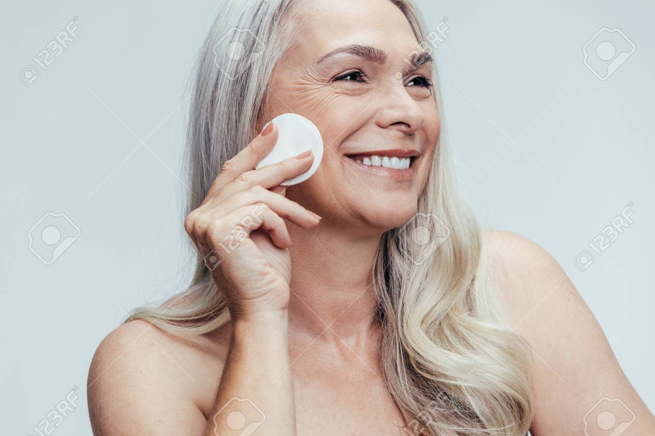 Smiling old woman cleansing her face with a cotton pad against grey background. Happy female cleaning her face skin with a cotton pad. - 122866000