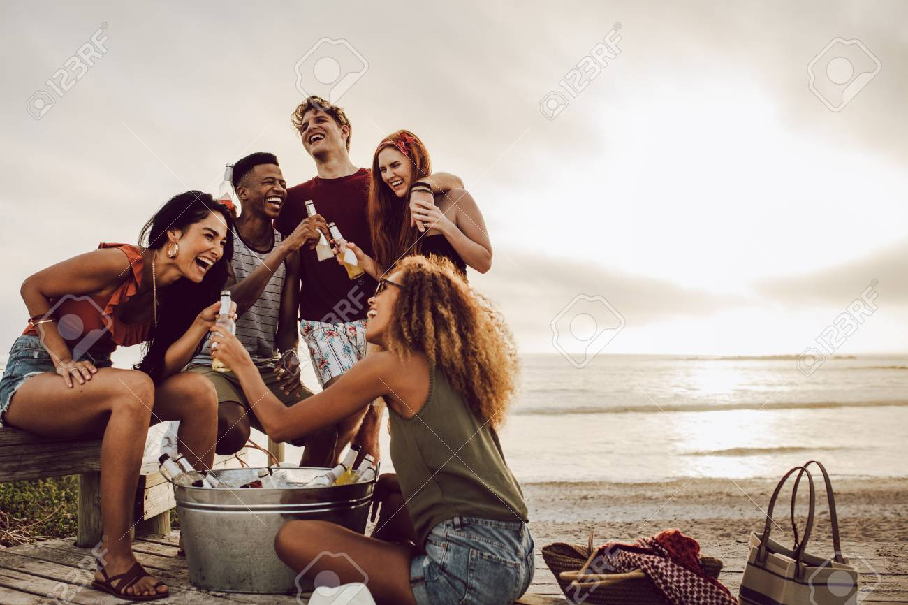 Smiling young woman with beer bottle and friends standing by on the beach. - 124972526
