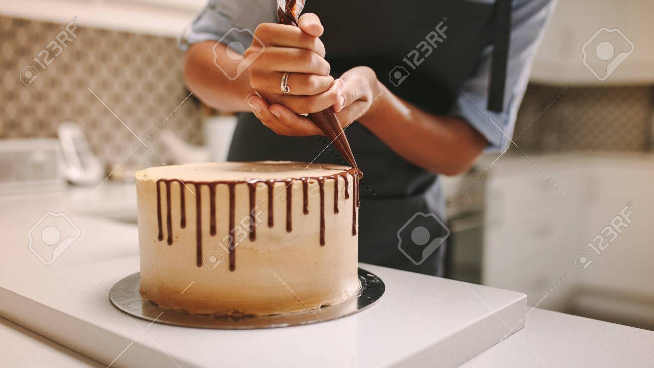 Close up of hands of a female chef with confectionery bag squeezing liquid chocolate on cake. - 124105087