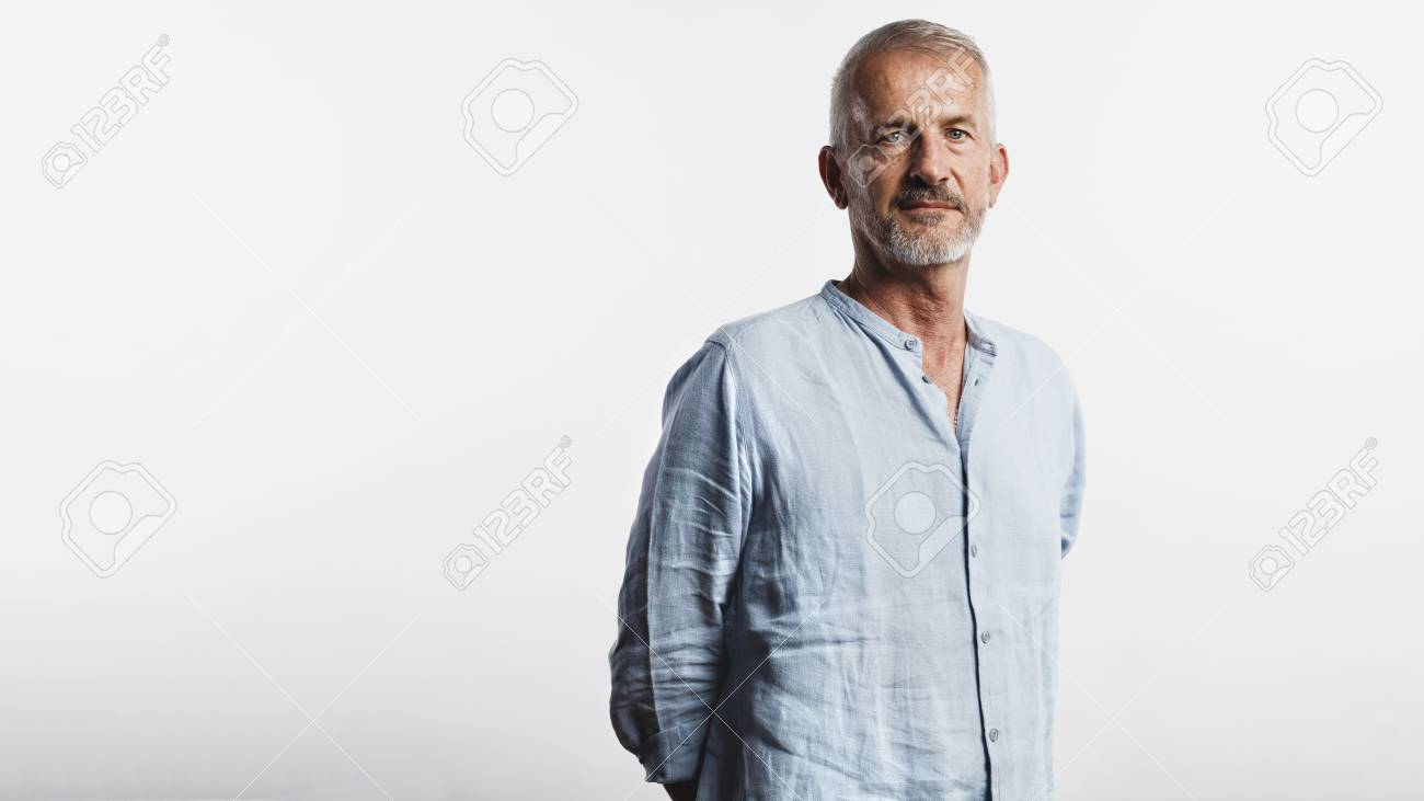 Old man standing with his hands behind him looking at camera. Portrait of a senior man standing against white background. - 125958021