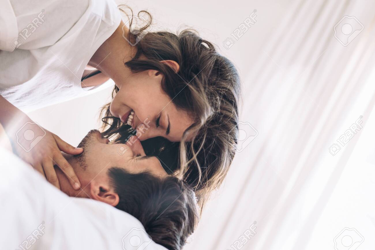 Romantic young couple in love on bed. Beautiful couple about to kiss. - 127399171