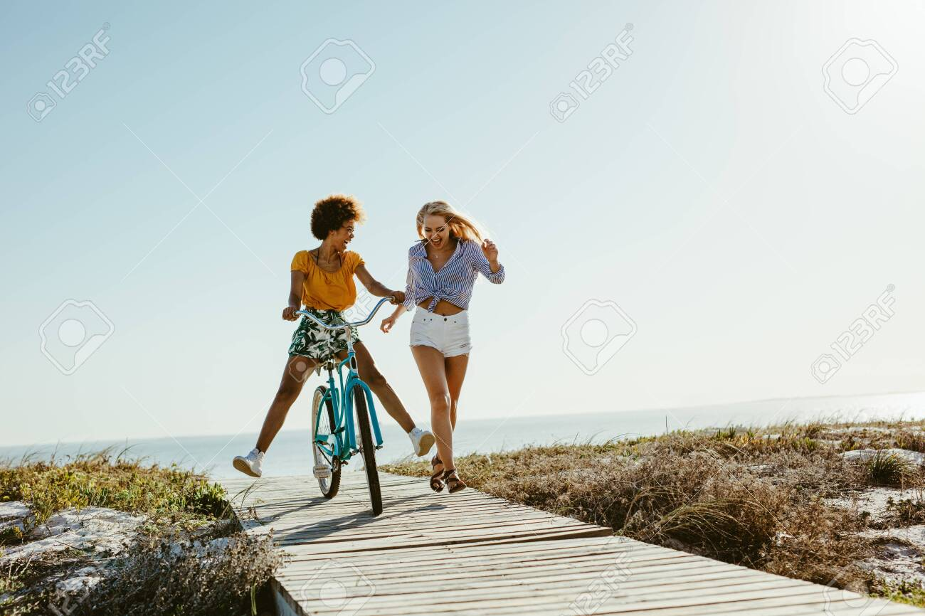 Two young women having fun with a bicycle at the beach. Woman running with friend riding a bike on boardwalk. - 127401806