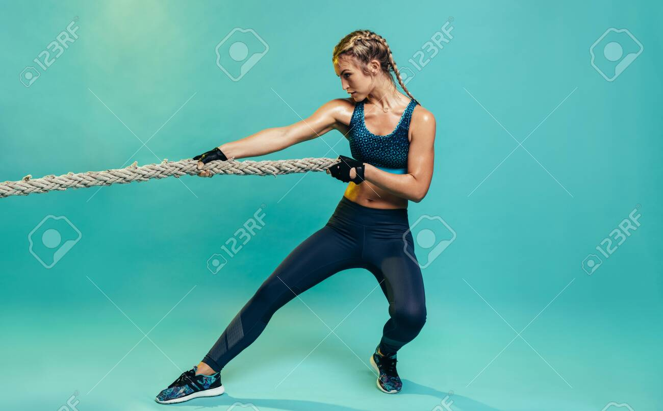 Tough young woman exercising with battling rope in studio. Healthy sports woman working out with battle rope over blue background. - 127402015