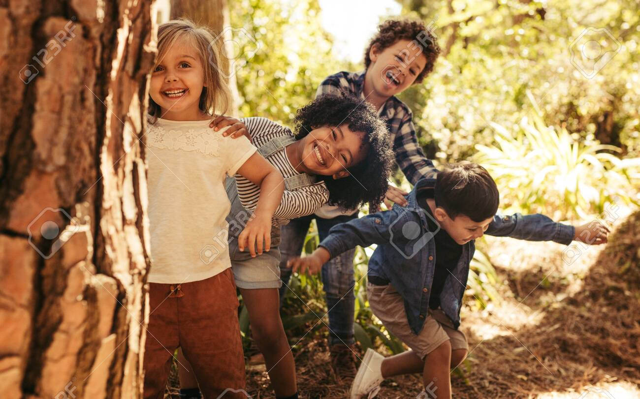 Cute smiling kids peeking out from behind the tree in the park. Group of children enjoying playing hide and seek in a forest. - 127853839