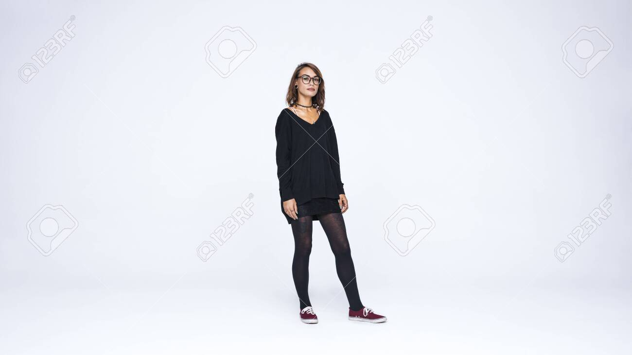 Woman in eyeglasses isolated on white background. Fashionable woman with pierced lips and tattoo on hand looking at camera. - 140806166