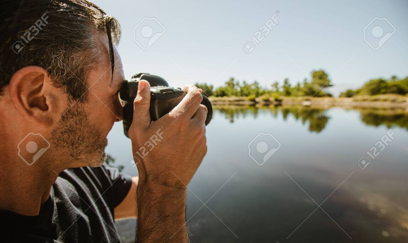 Closeup of a mature man taking photographs with a dslr camera of lake. Male photographer taking pictures of a lake. - 144191869