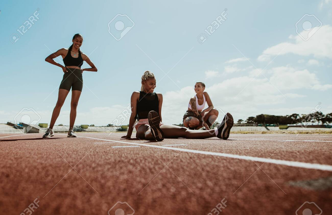 Female athletes taking a break after workout sitting on the running track in the stadium. Women relaxing and smiling after training. - 149004004