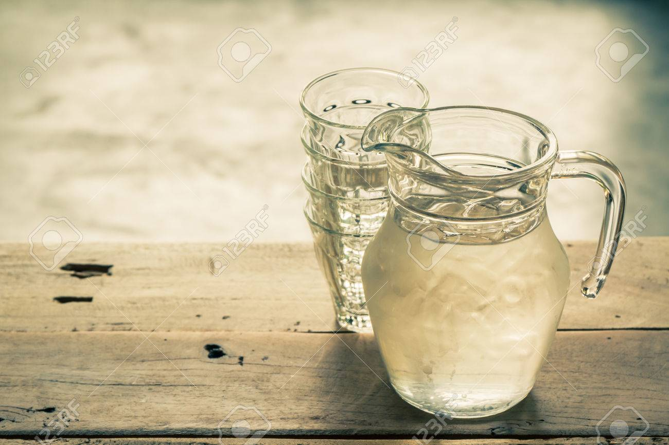 Bicchiere di vetro e la caraffa con acqua su un tavolo