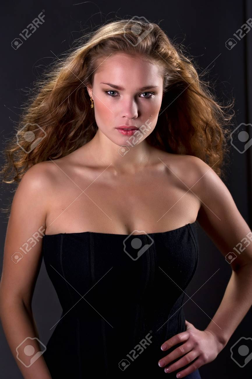 Young beautiful woman with long curly hairs isolated on black Stock Photo - 8294232