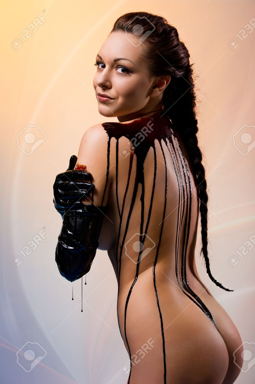 Naked young beautiful woman body covered with dark chocolate Stock Photo - 9560197