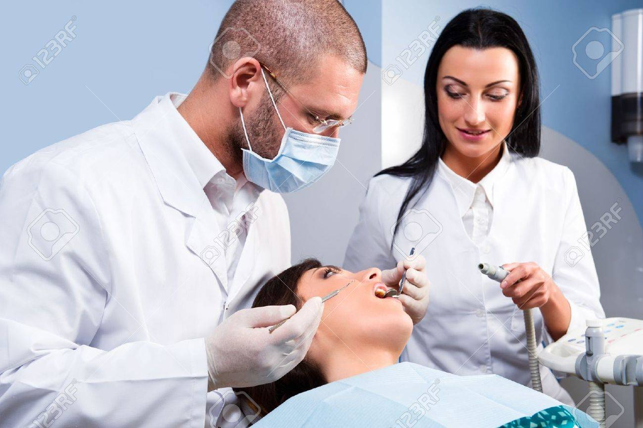 Male Dentist With Assistant And Patient At Dental Clinic Stock ...