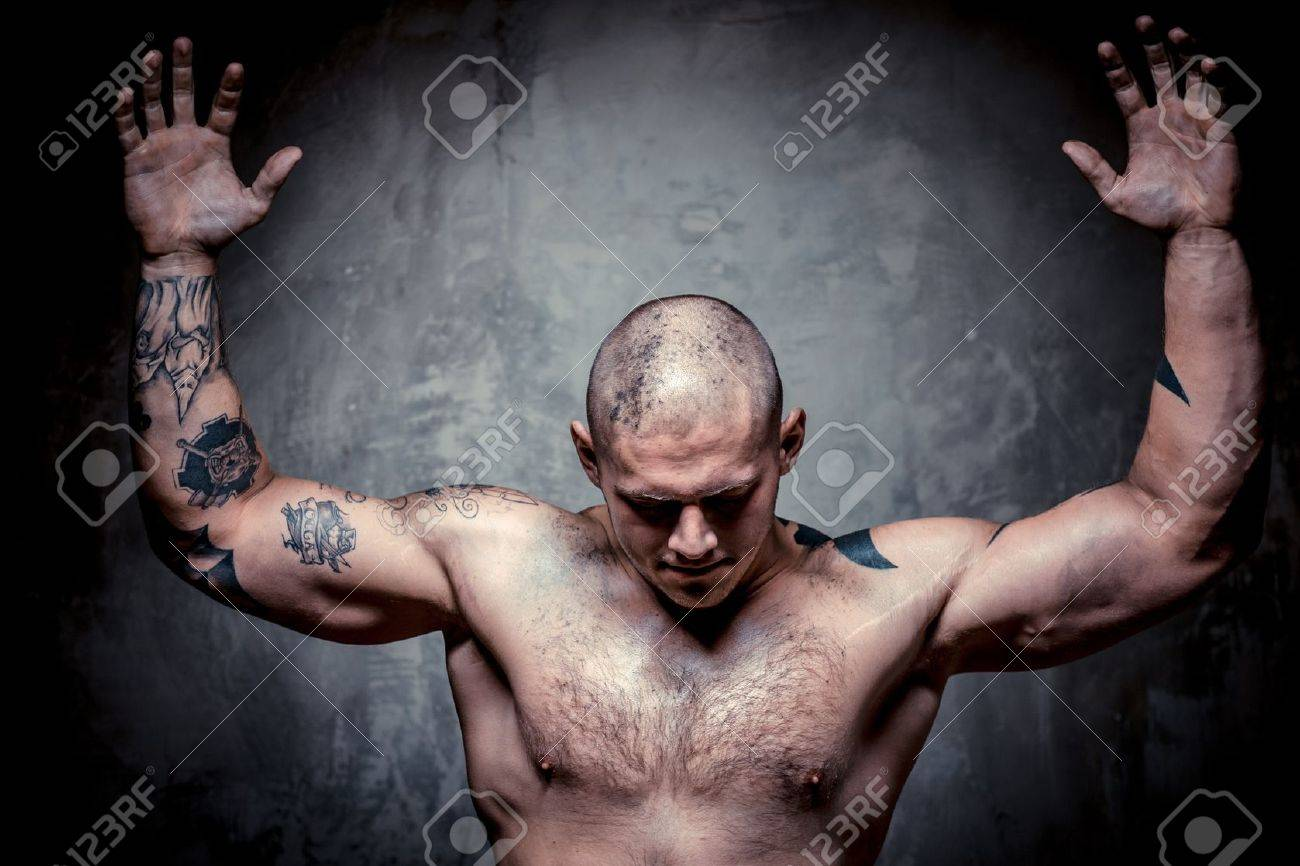 muscular tattooed man with hands raised up posing over grey
