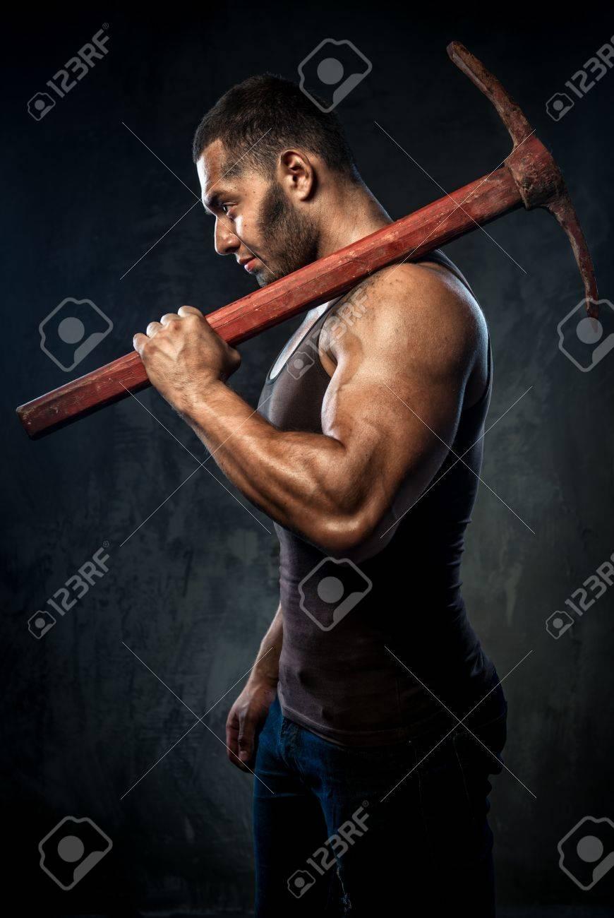 Muscular man holding pickaxe Stock Photo - 20834545