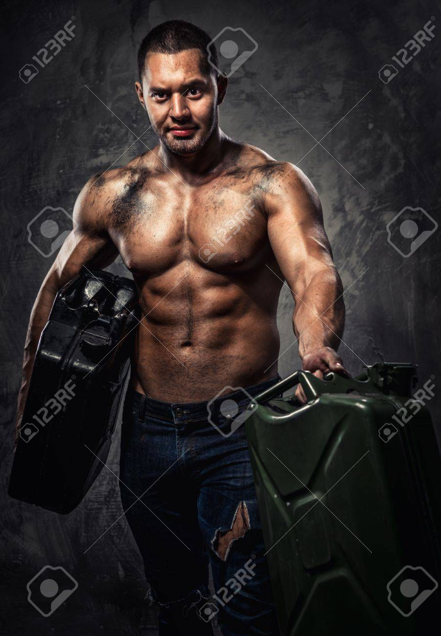 Muscular man with two metal fuel cans indoors Stock Photo - 20914434