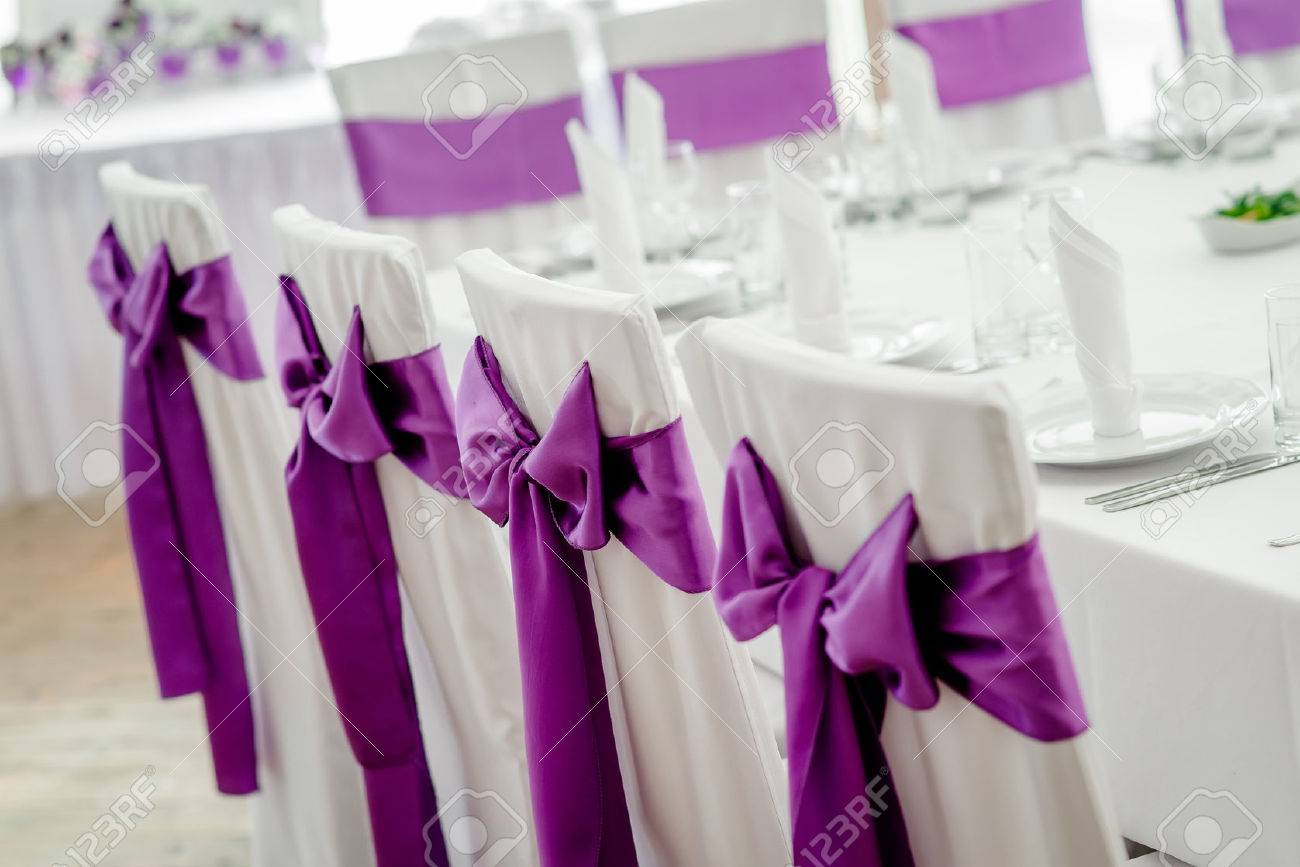 Close Up Of White Wedding Chairs With Purple Ribbon Stock Photo