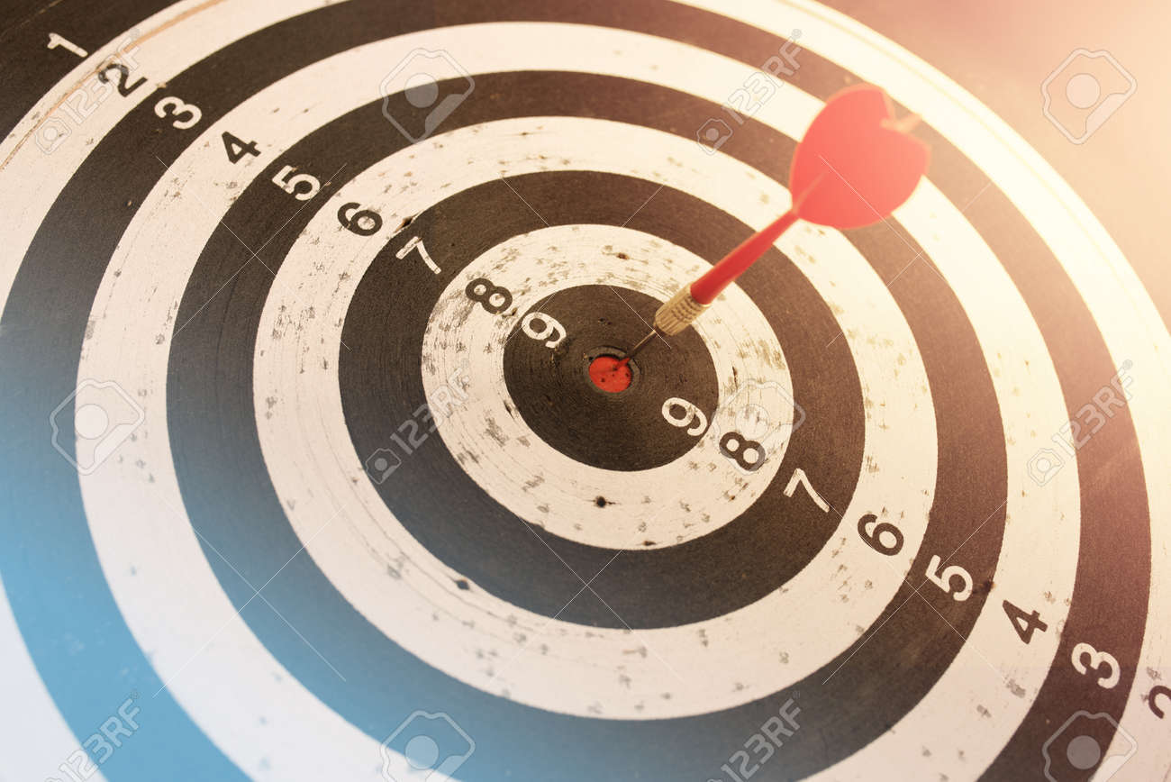Dart in bulls eye of dartboard with shallow depth of field concept for hitting target - 169218033
