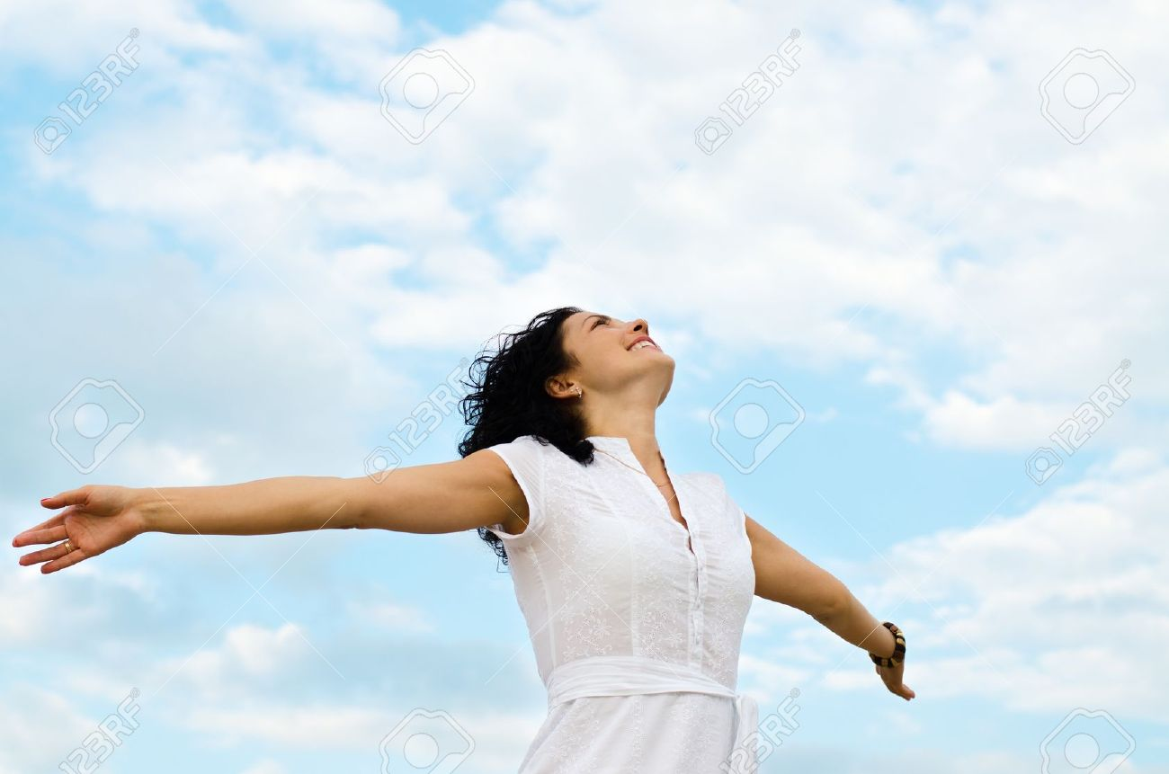 Happy smiling woman standing with outspread arms and her face lifted to the cloudy blue sky - 14615066