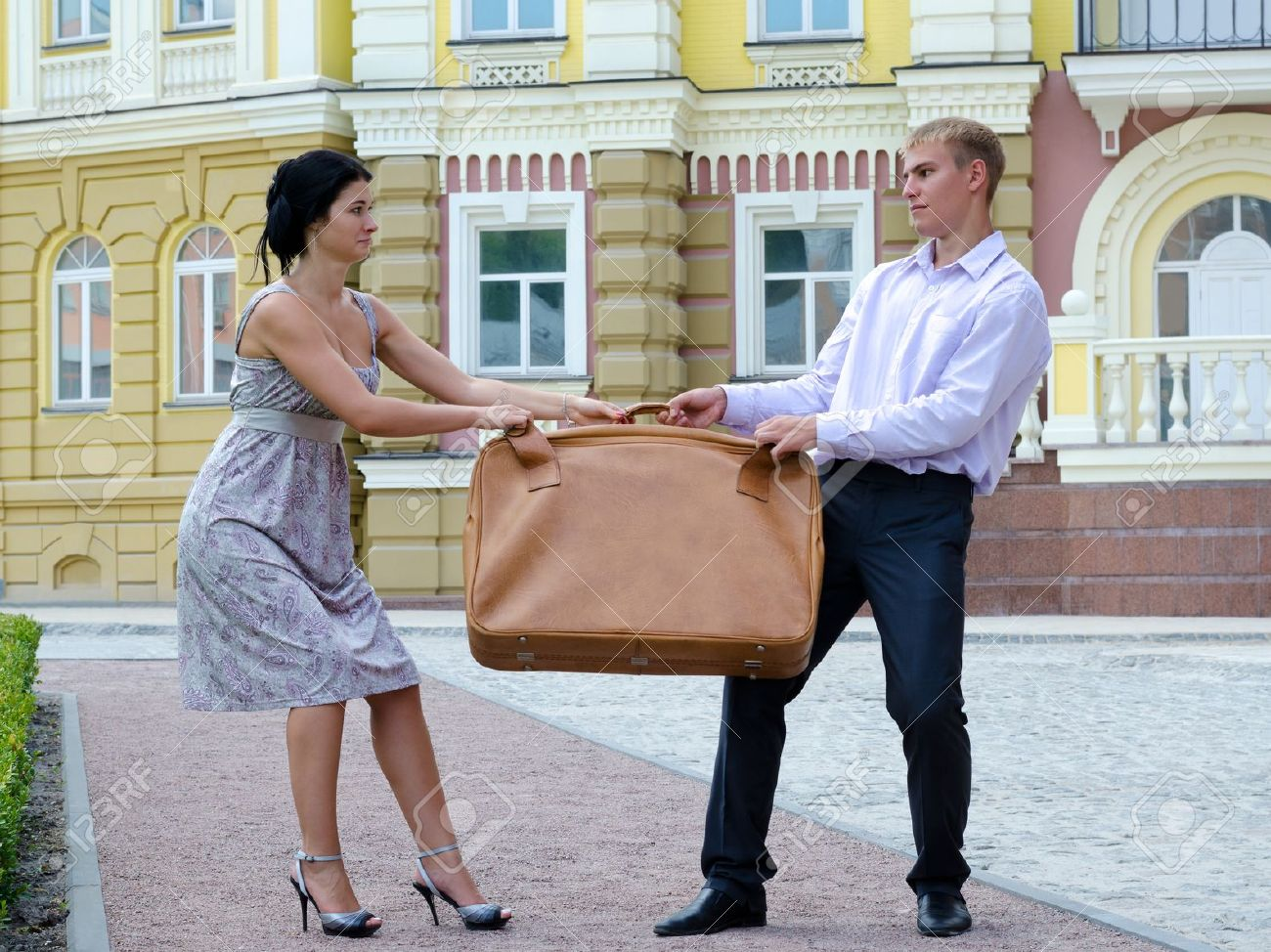 Stylish young couple fighting over luggage and playing tug of war with a large suitcase on an urban street Stock Photo - 14738934