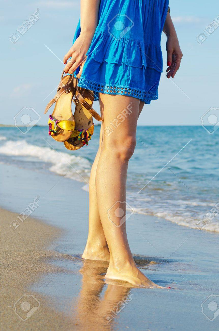 Woman holding her sandals in her hands while standing in wet sand at the edge of the surf on a beach - 14889376