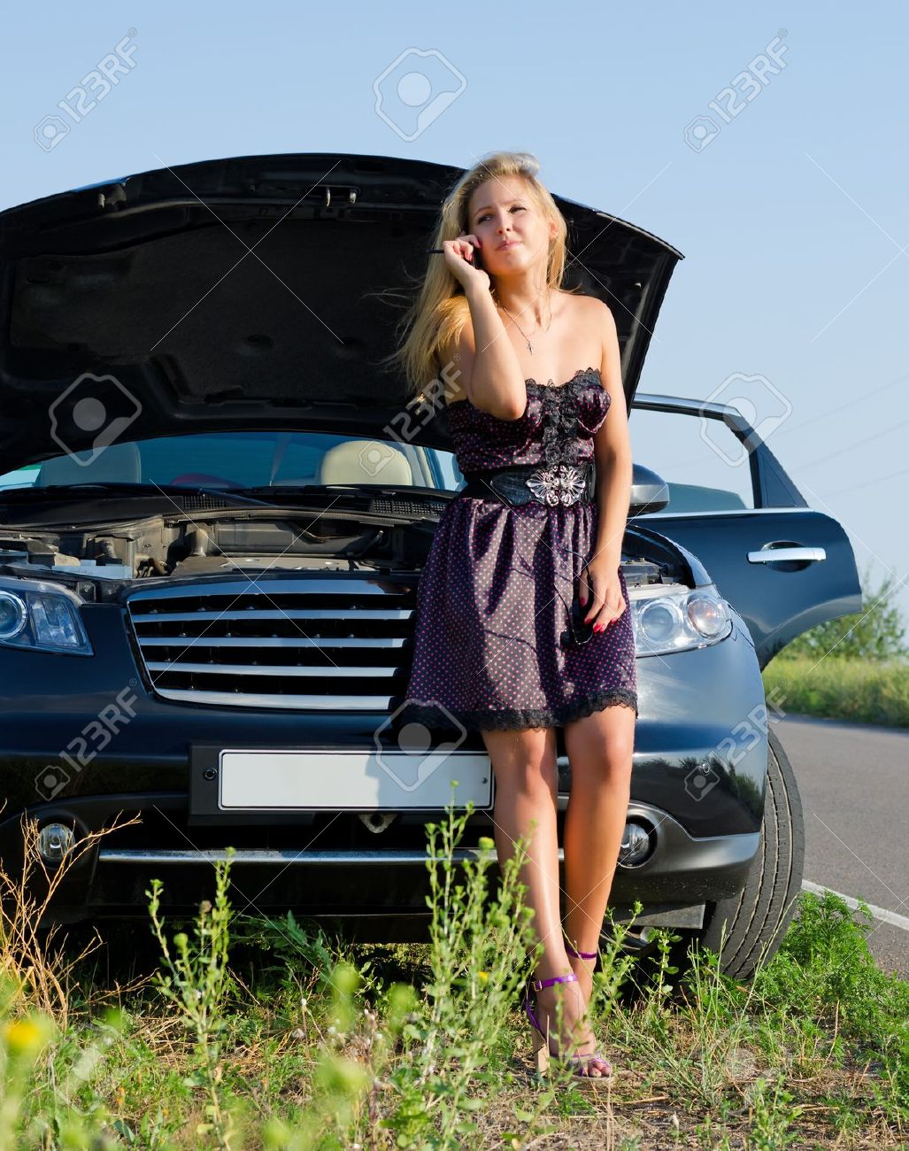 Fashionable young woman phoning for help on her mobile as she leans against her car which has broken down in the countryside - 14894197
