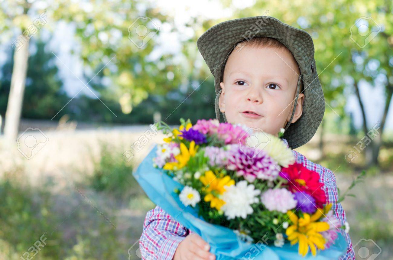Cute little boy in cowboy style sunhat with a floral bouquet of assorted colourful flowers in woodland with copyspace Stock Photo - 15277420