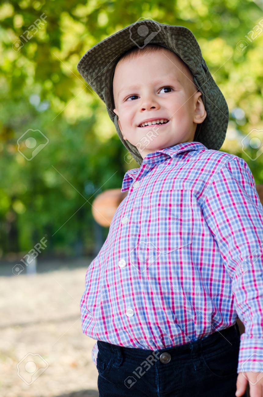 Closeup of a happy little boy in a cowboy style hat playing outdoors in the park with green trees Stock Photo - 15455250