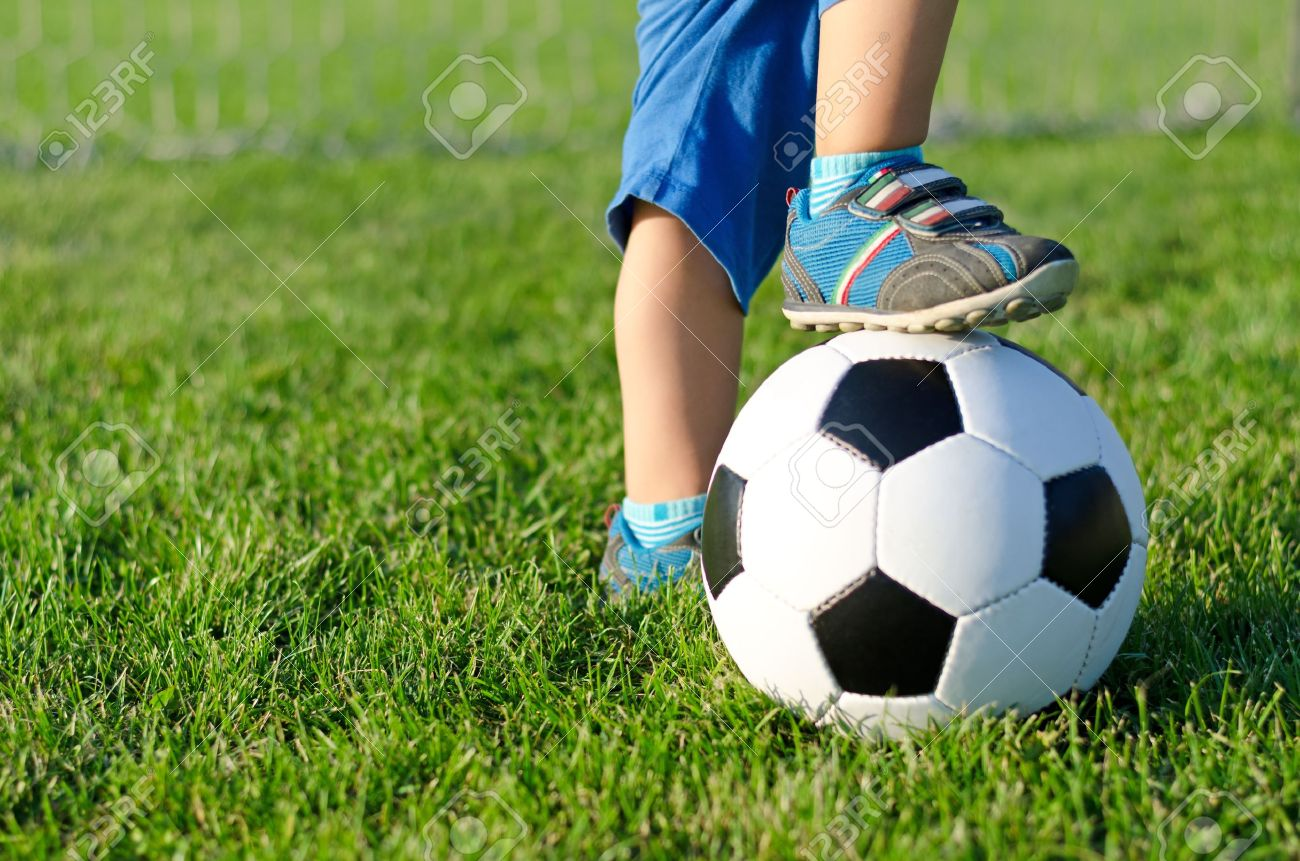 Little boy in shorts and trainers with his foot resting on top of a soccer ball on green grass with copyspace - 15887740