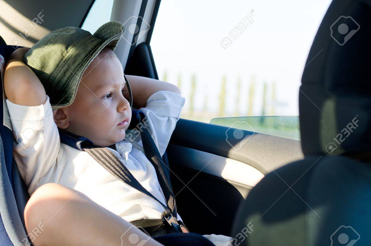 Little boy in a child safety seat sitting patiently in the back of a car with his hands behind his head staring out of the window Stock Photo - 17657752