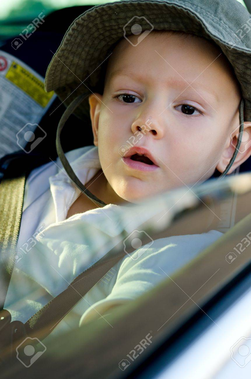 Adorable little boy wearing a hat waiting in a car strapped into a child safety seat and peering out of the open passenger window Stock Photo - 17703276