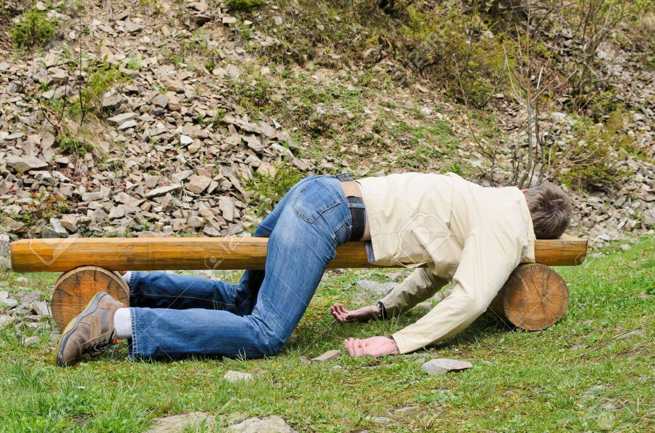 Young man deeply sleeping or drunk, laying outdoors on a wooden park bench Profile view - 19800488