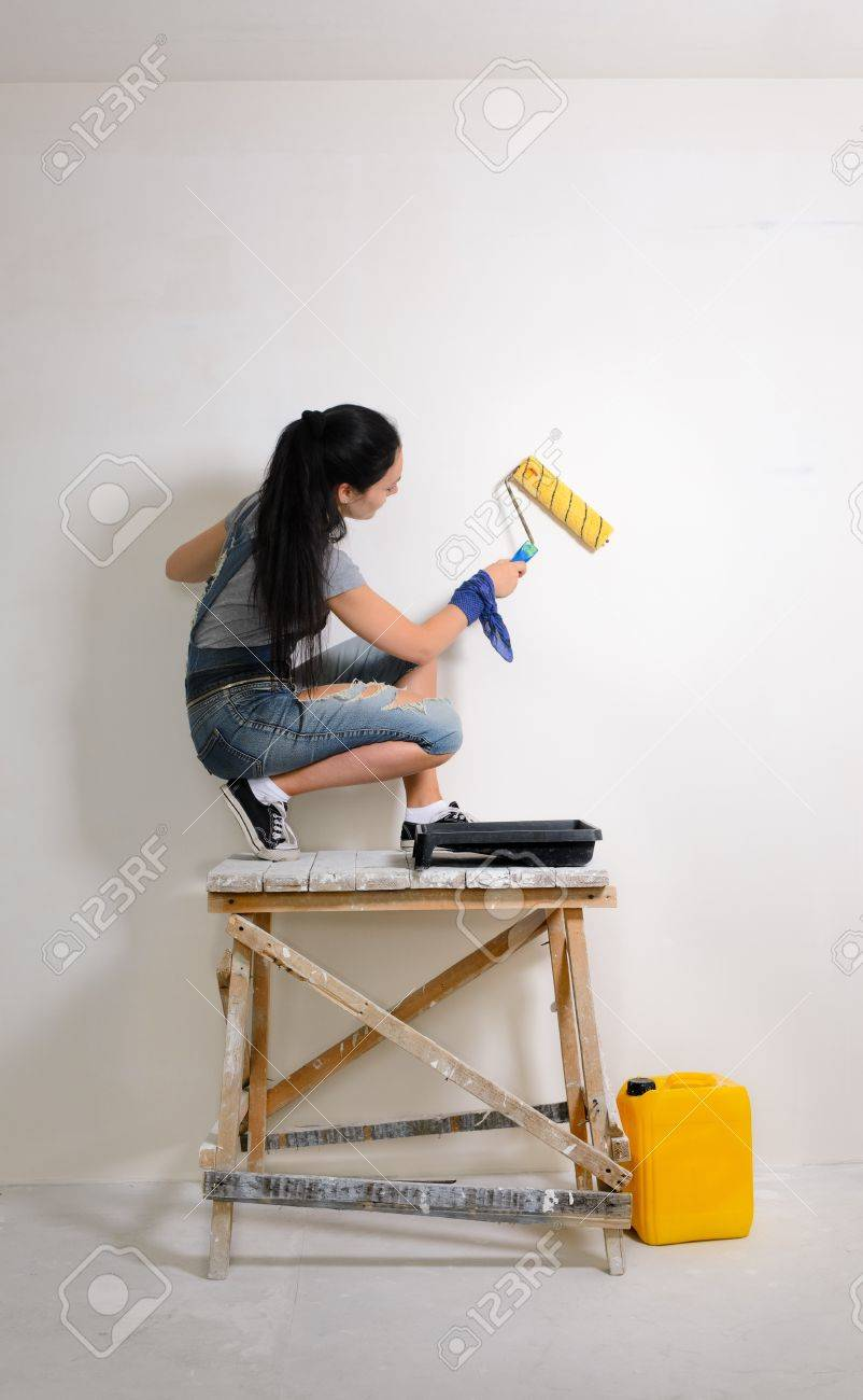 Stock Photo Young Girl Crouched On A Wooden Trestle Painting The Wall While Redecorating The House
