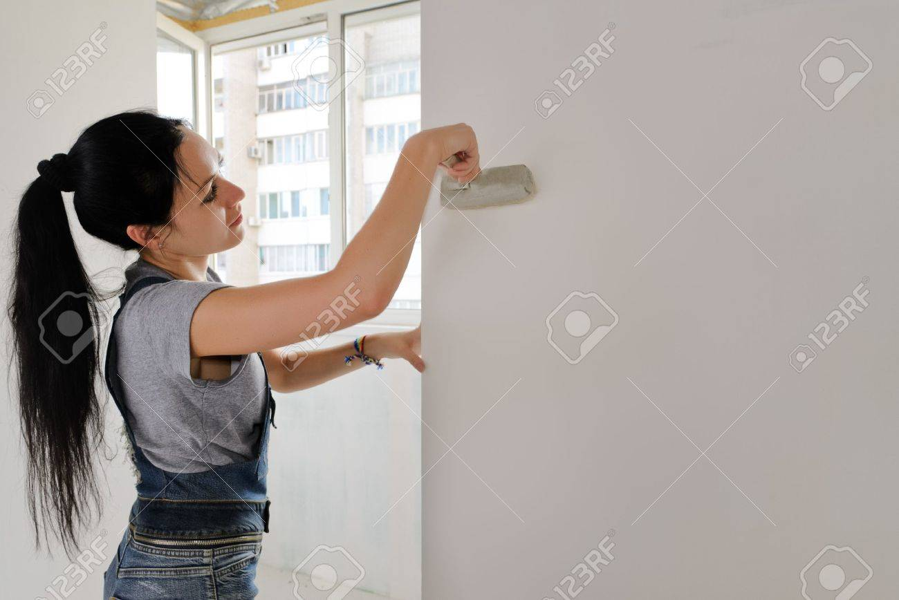 Woman painting an apartment wall finishing off the redecorating with a paintbrush - 20691930