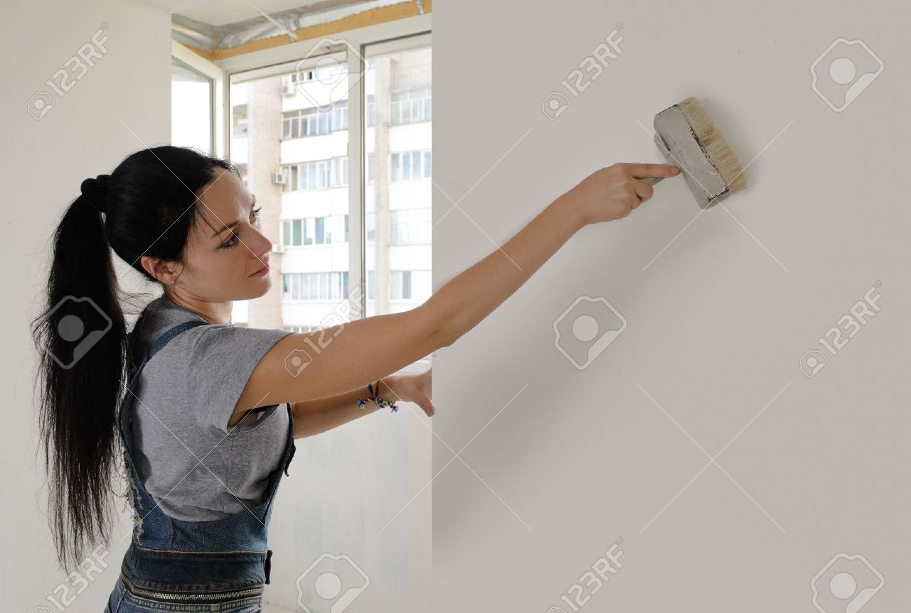 Attractive Young Woman Redecorating Her House Painting A Wall With A Brush  With Copyspace Stock Photo