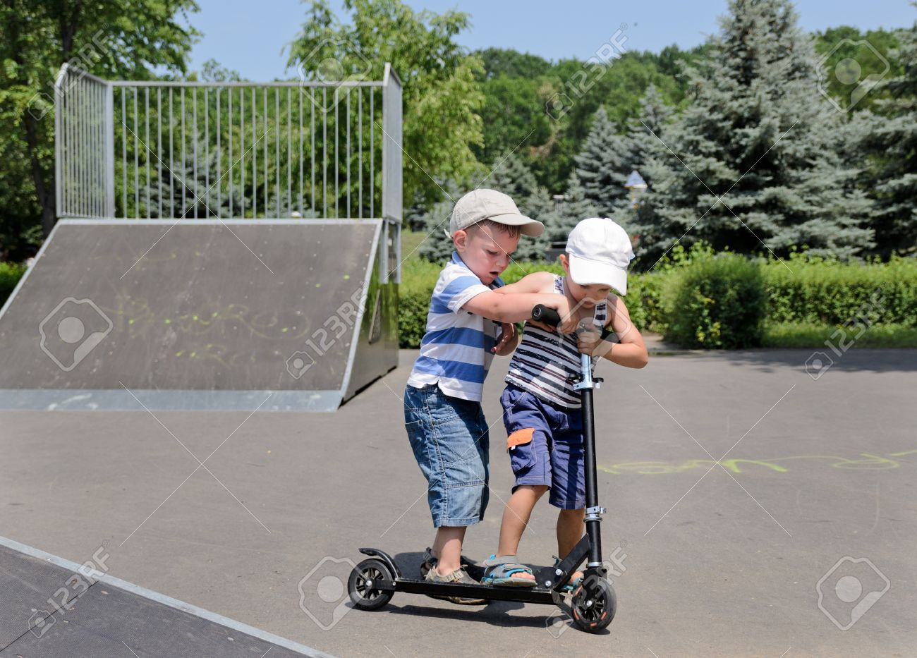 Two small boys standing arguing and fighting over who will get to ride a scooter in the skate park - 21329690